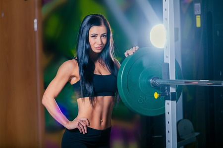La chica joven atractiva que se reclina después de ejercicios en cuclillas. Fitness mujer morena.