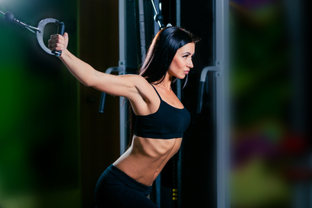 crossover: young fitness woman execute exercise with exercise-machine Cable Crossover in gym, horizontal photo.
