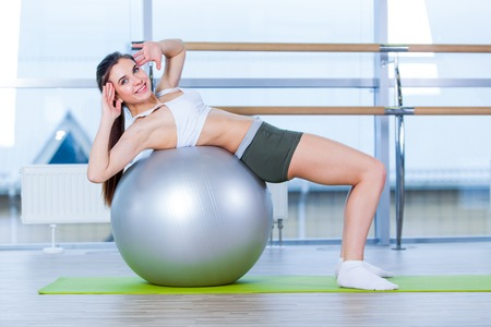 fit ball: Beautiful young girl doing exercises with fit ball at gym Stock Photo