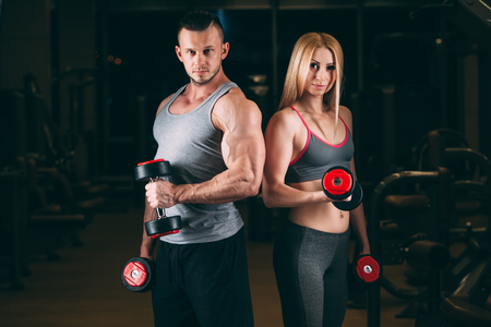 beautiful young sporty sexy couple showing muscle and workout in gym. dumbbell Фото со стока