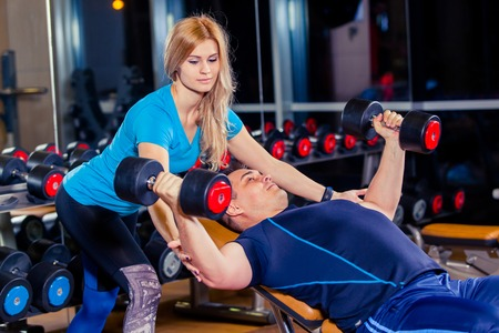 strengthen hand: Personal trainer woman helping men working with heavy dumbbells