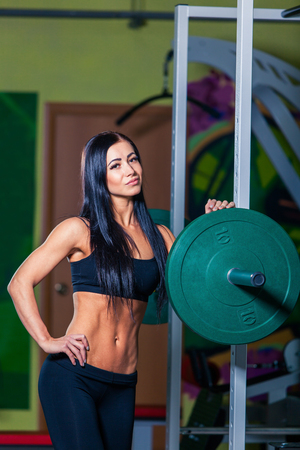 squat: sexy young girl resting after squat exercises. Fitness brunette woman. Stock Photo