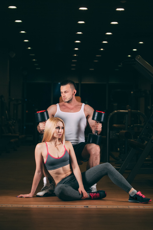 beautiful young sporty couple showing muscle and workout in gym. dumbbell Reklamní fotografie
