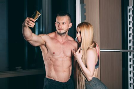 snapshots: Young couple exercising in gym with weights  man, selfie, Snapshots on the phone