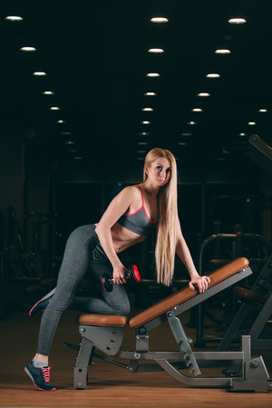 brutal: Brutal athletic woman pumping up muscles with dumbbells in gym.