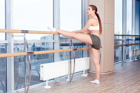 barre: Woman standing near barre in fitness center. Stock Photo