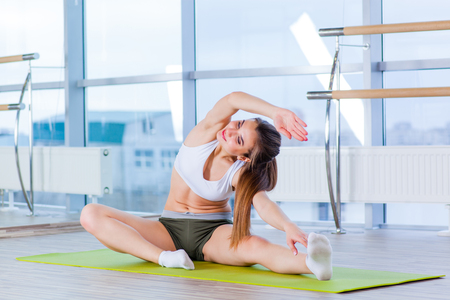 fitness, sport, training and people concept -  Happy young woman stretching before running in gym.