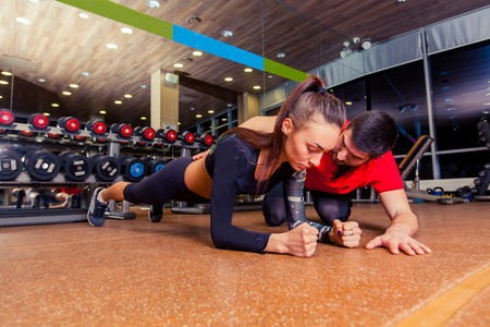 plank position: Trainer supervising a muscular woman doing plank exercises, exercise strap