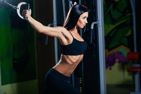 musculation: young fitness woman execute exercise with exercise-machine Cable Crossover in gym, horizontal photo.