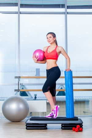 additional training: Fitness girl, wearing in sneakers, red top and black  breeches, posing on step board with ball, on the sport equipment background, in the gym.