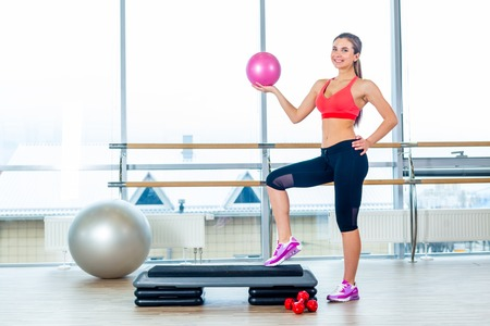 breeches: Fitness girl, wearing in sneakers, red top and black  breeches, posing on step board with ball, on the sport equipment background, in the gym.