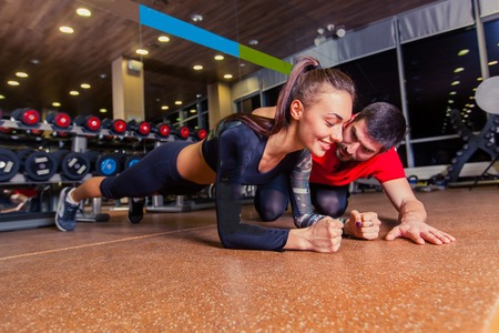 Trainer supervising a muscular woman doing plank exercises, exercise strap