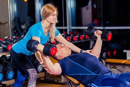 Personal trainer woman helping men working with heavy dumbbells