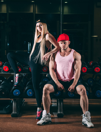 sport, bodybuilding, weightlifting, lifestyle and people concept - Young beautiful couple in stylish clothes sitting in a gym near the dumbbells.