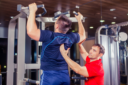 calisthenics: sport, fitness, teamwork, bodybuilding people concept - man and personal trainer with barbell weight lifting group weightlifting workout exercise gym Stock Photo