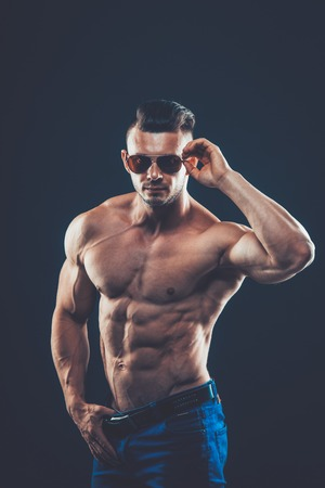 nipple man: strong athletic man  in sunglasses on black background. To pump the abdominals.