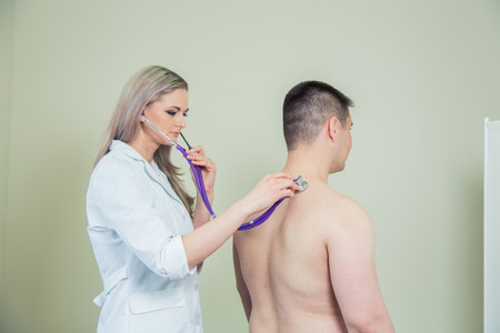 hospital patient: Hospital: Physician Checks man Patient With Stethoscope Stock Photo
