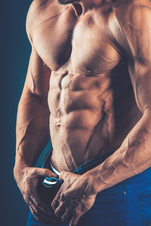 abdominals: strong athletic man   on black background. To pump the abdominals.