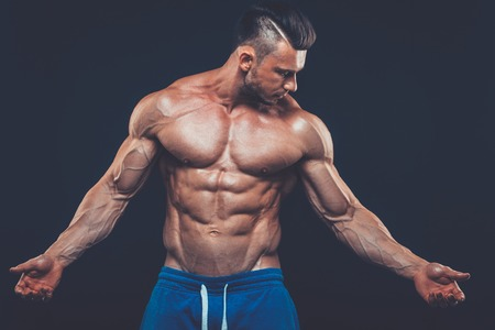 nipple man: strong athletic man on black background. fitness Stock Photo