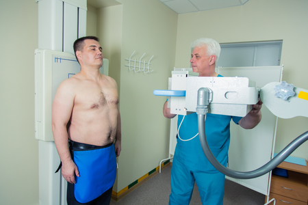 radiographic: Mid adult men patient  mature male doctor setting up the machine to take x-ray