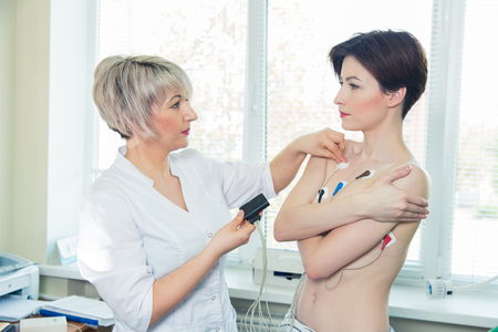 heart monitor: Young woman wearing a Holter Heart Monitor.