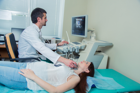 woman getting ultrasound of a thyroid from doctor.