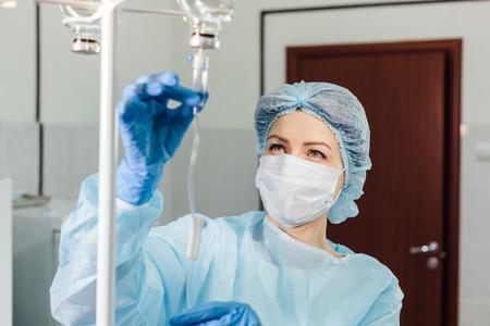 Enfermera conectar un goteo intravenoso en la habitación del hospital