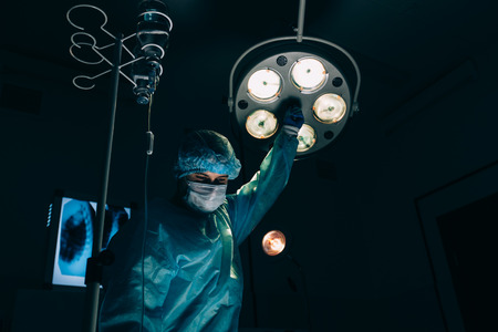 resuscitate: surgery, medicine and people concept - surgeon in mask adjusting lamp in operating room at hospital