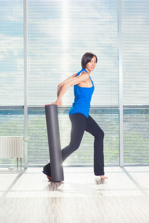 blonde minority: fitness, sport, training and lifestyle concept - woman doing pilates on the floor with foam roller.