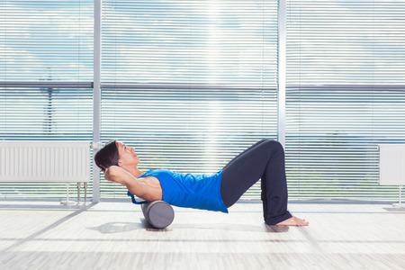 fitness, deporte, la formación y el concepto de estilo de vida - haciendo Pilates de la mujer en el suelo con rodillo de espuma.