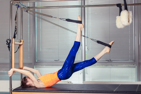 Healthy Smiling Woman Wearing Leotard Practicing Pilates in Bright Exercise Studio. Фото со стока