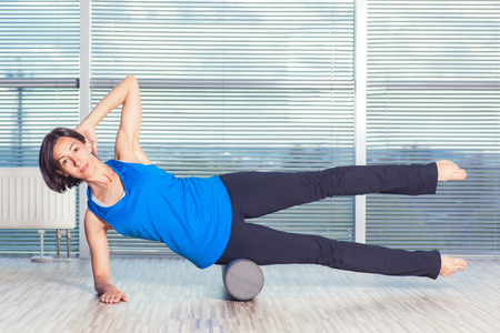 fitness, sport, training and lifestyle concept - woman doing pilates on the floor with foam roller.