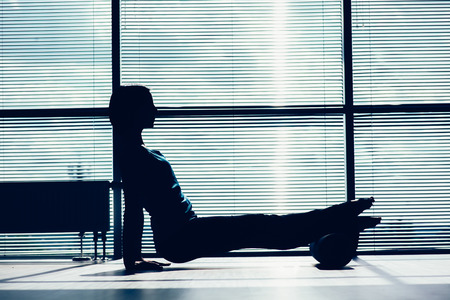fitness, sport, training and lifestyle concept - woman doing pilates on the floor with foam roller. contour of the body against the window Фото со стока
