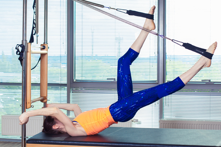 reformer: Healthy Smiling Woman Wearing Leotard Practicing Pilates in Bright Exercise Studio. Stock Photo