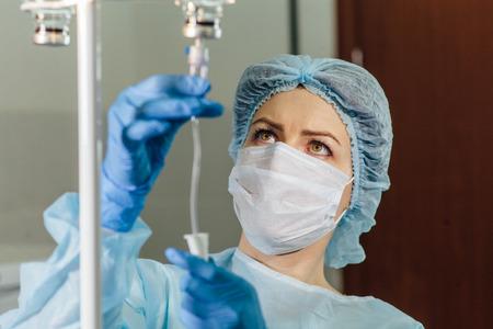 Enfermera conectar un goteo intravenoso en la habitación del hospital Foto de archivo