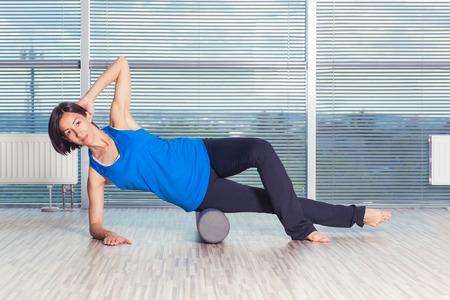 fitness, deporte, la formación y el concepto de estilo de vida - haciendo Pilates de la mujer en el suelo con rodillo de espuma. Foto de archivo