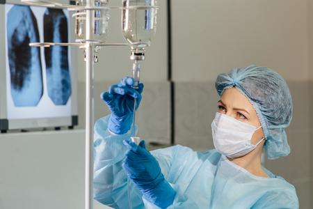 Mujer médico ajustar botella de infusión en el hospital. Foto de archivo