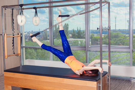trapeze: Healthy Smiling Woman Wearing Leotard Practicing Pilates in Bright Exercise Studio. Stock Photo