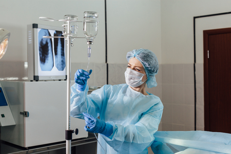 chemo: Nurse connecting an intravenous drip in hospital room