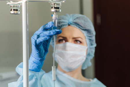 chemo: Female doctor adjusting infusion bottle in hospital.