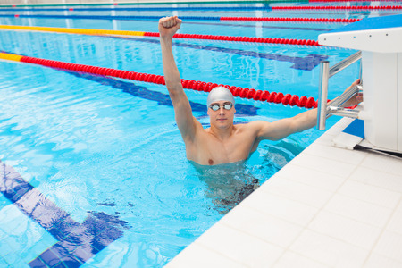 swim goggles: Sport swimmer winning. Man swimming cheering celebrating victory success smiling happy in pool wearing swim goggles and gray swimming cap. Caucasian male fit fitness model. Stock Photo