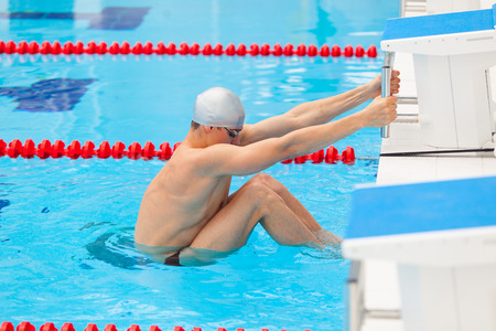 profundity: Young man in a pool - go to start swimming. backstroke during.