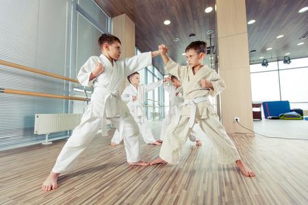 mujer deportista: jóvenes, bellas y exitosas de varios niños de karate éticos en la posición de karate Foto de archivo