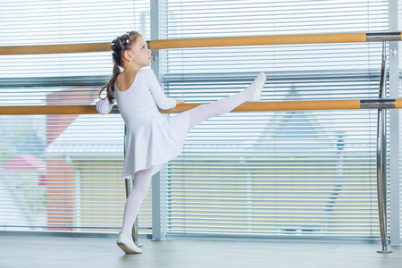 art lessons: Little ballerina girl. Adorable child dancing classical ballet in a white studio. Children dance. Kids performing. Young gifted dancer in a class. Preschool kid taking art lessons.