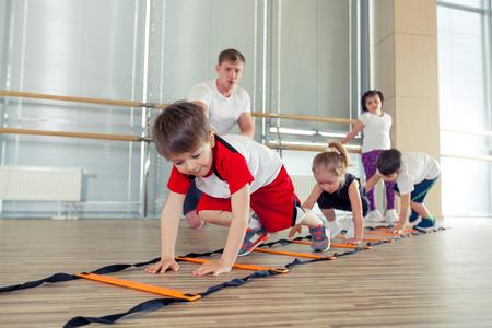 Happy sporty children in gym. pressing, working with a coach. childrens fitness Zdjęcie Seryjne