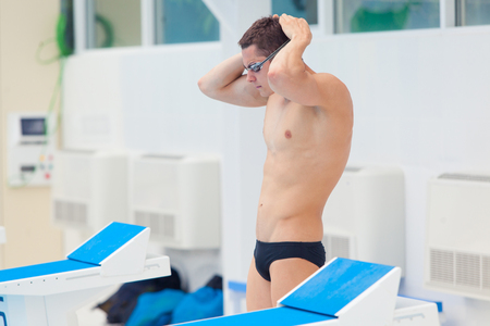 profundity: Young muscular swimmer preparing to start, puts his hat and glasses Stock Photo