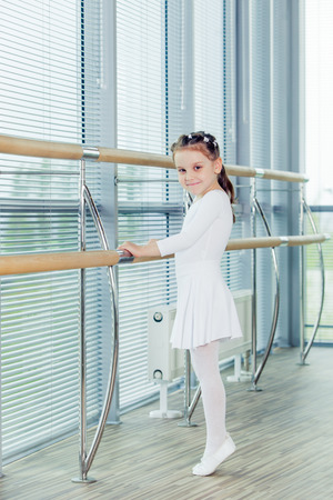 ballerina tights: Little ballerina girl. Adorable child dancing classical ballet in a white studio. Children dance. Kids performing. Young gifted dancer in a class. Preschool kid taking art lessons.