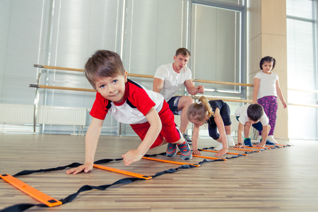 Happy sporty children in gym. pressing, working with a coach. childrens fitness Stock Photo