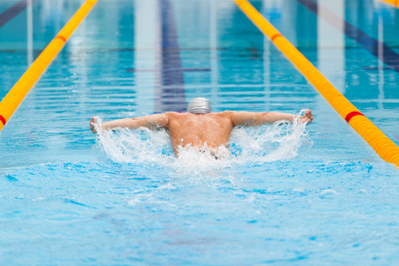 front raise: dynamic and fit swimmer in cap breathing performing the butterfly stroke.