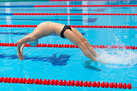 profundity: Young muscular swimmer jumping from starting block in a swimming pool.